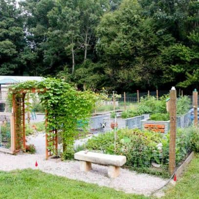 A concrete bench sits outside a fenced in raised bed garden.