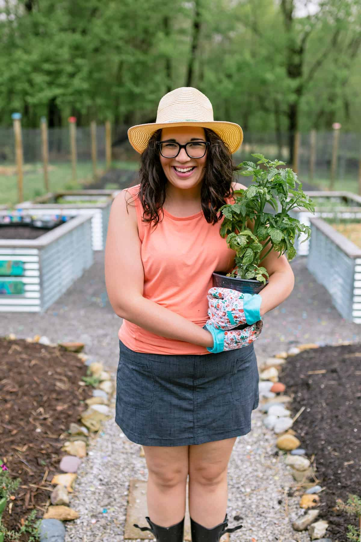 Brunette woman standing in a garden and holding a tomato plant, smiling