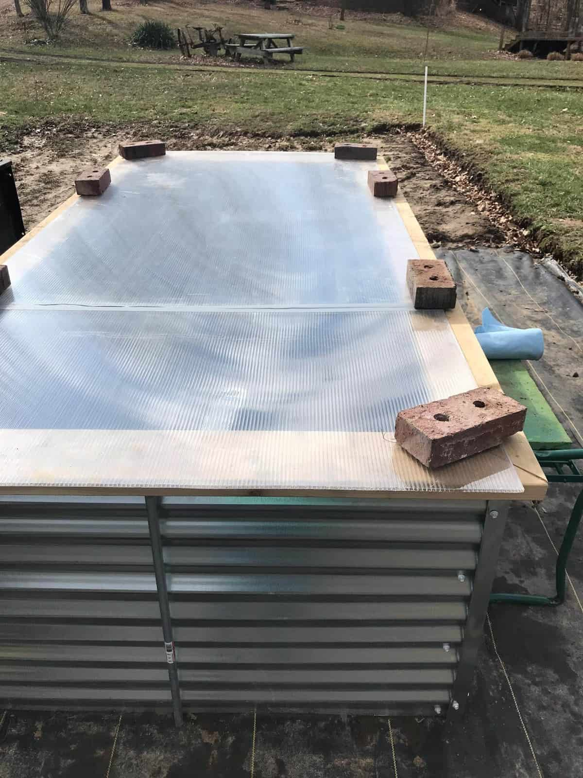 Side shot of a Galvanized Steel Raised Garden Bed with a greenhouse panel laid over top, held down with bricks