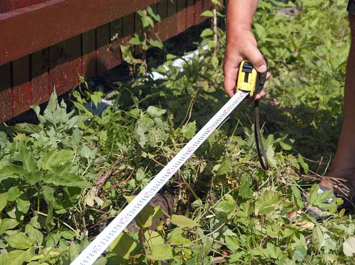 A hand uses a measuring tape to measure a gardening space