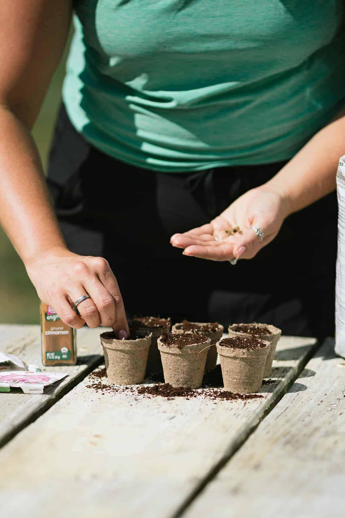 How to start seeds indoors: A woman plants seeds in peat pots.