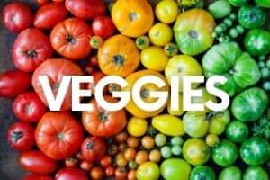 "Heirloom tomatoes arrayed in rainbow order. A text overlay says ""Veggies."""