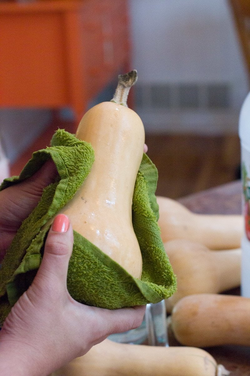 Hands use a green dish towel to dry a butternut squash