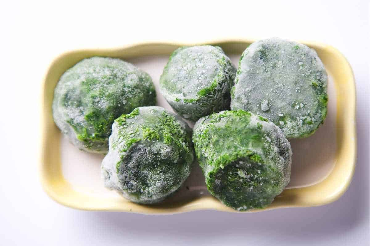 Cylinders of frozen spinach that were packed into a muffin tin sit on a yellow tray