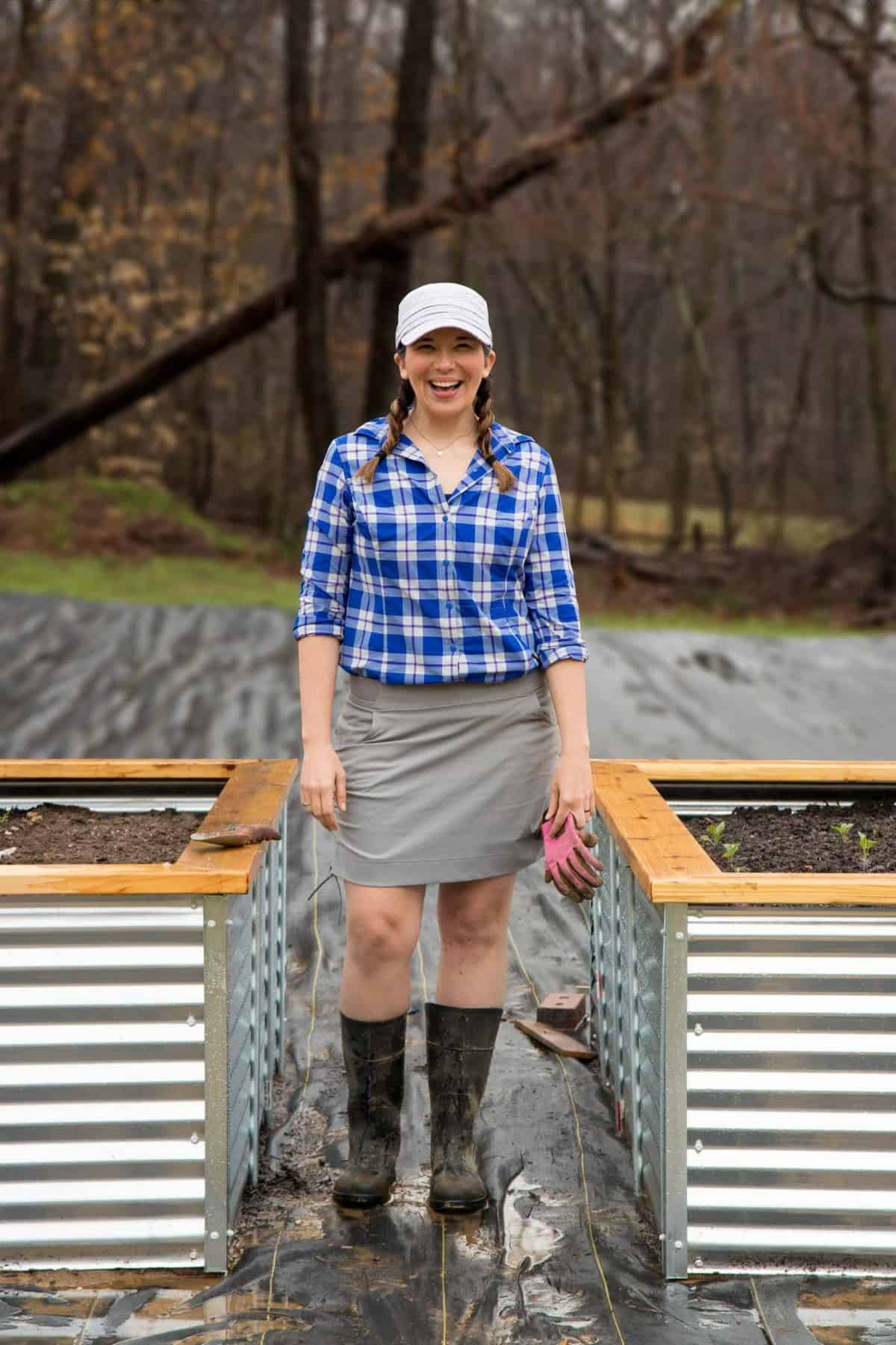 Woman standing between two raised beds, smiling