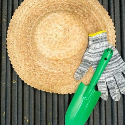 A green trowel and a striped garden glove sits on top of a straw gardening hat