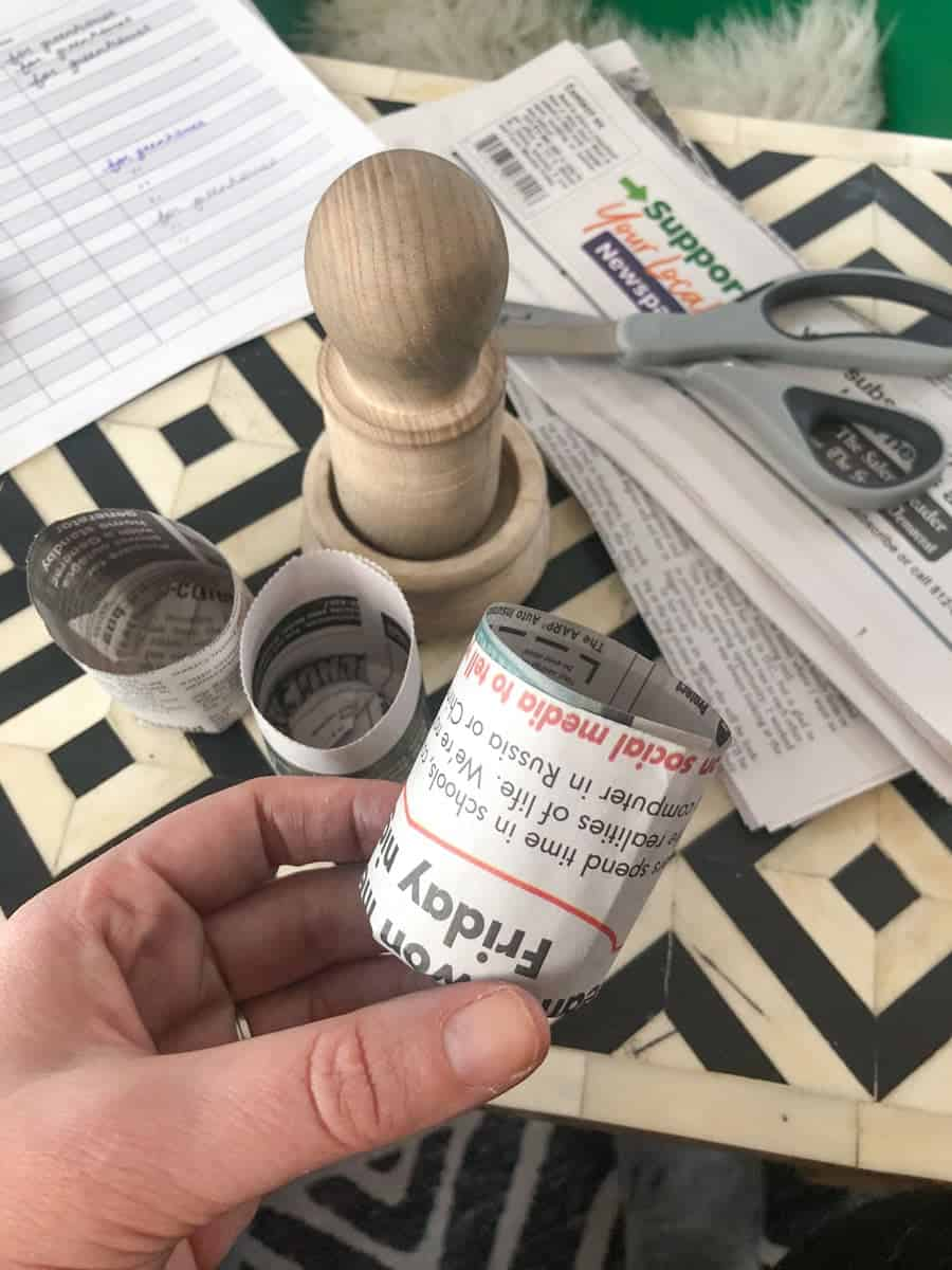 A hand holds a small pot meant for seedlings, made out of newspaper. Newspaper, scissors, and a pot maker are in the background.