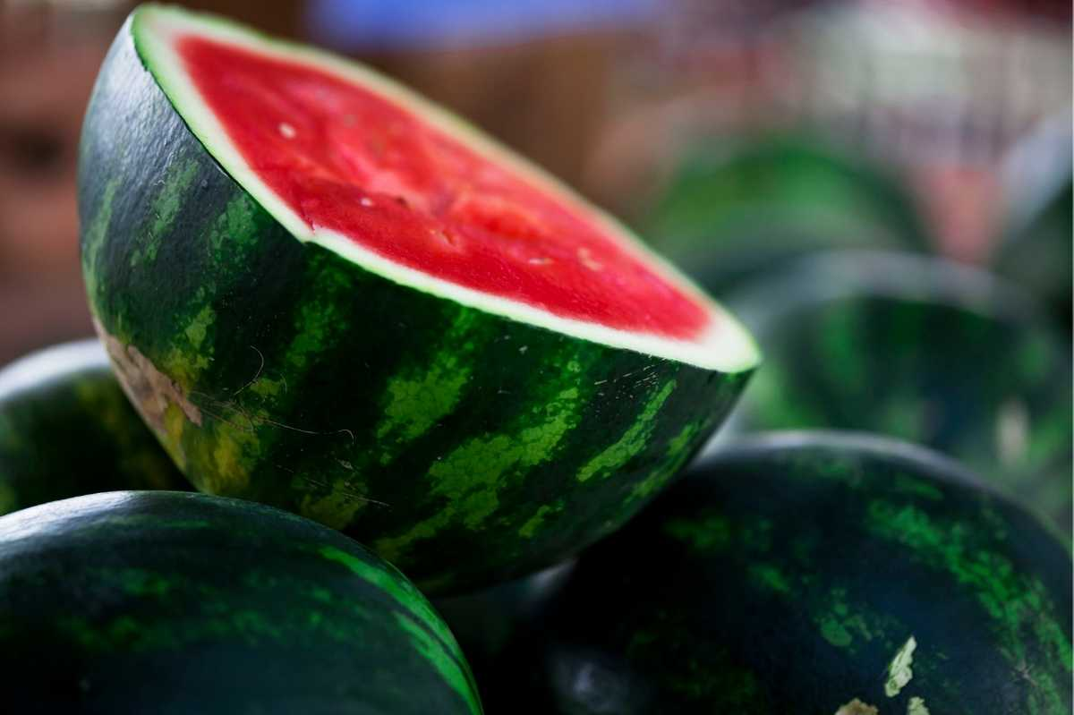 A halved ripe watermelon sits on top of other whole watermelon