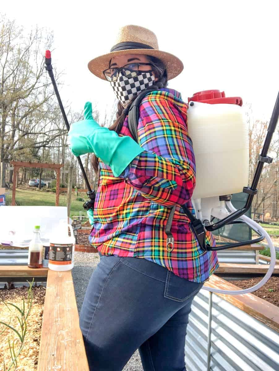 A woman in protective gear and a backpack sprayer gives a thumbs up to the camera