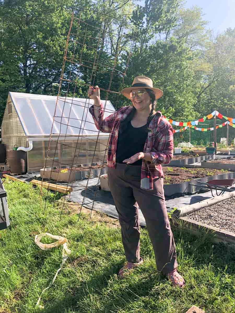 A woman in braids holds up a tomato cage made out of remesh