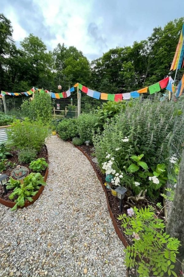 A pollinator garden with prayer flags and a weed-free gravel aisle